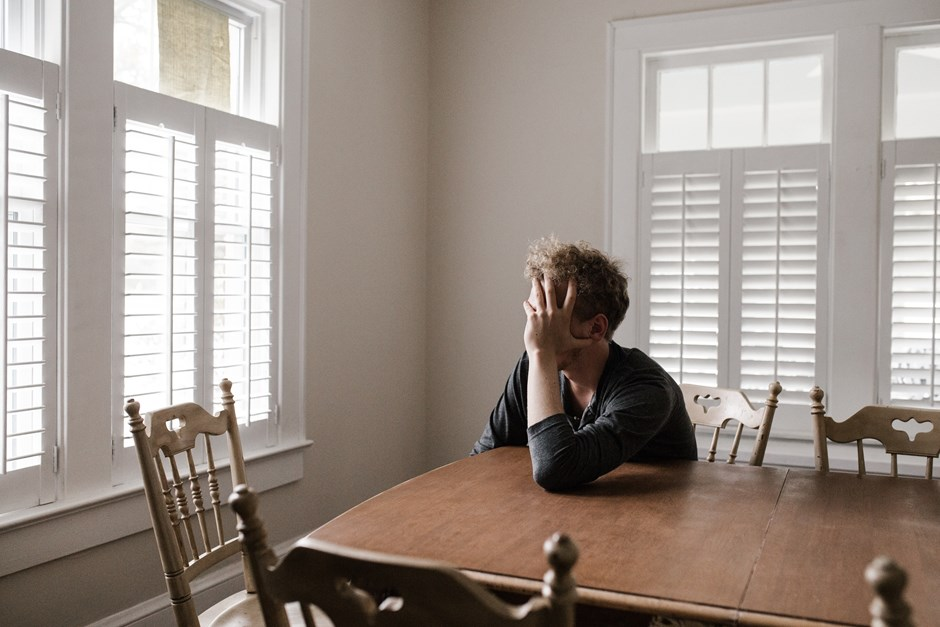 Photo of man sitting at kitchen table holding his head in his hands